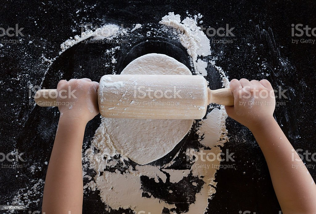 The kid rolls out the pizza dough stock photo