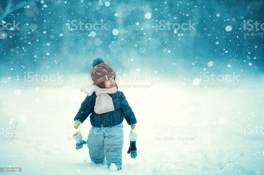 the kid walks in snow stock photo