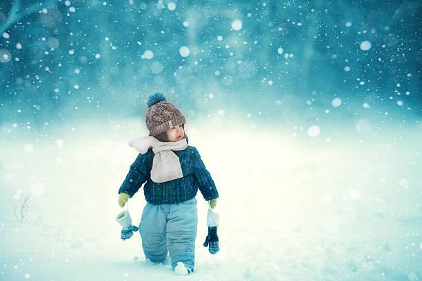 the kid walks in snow stock photo