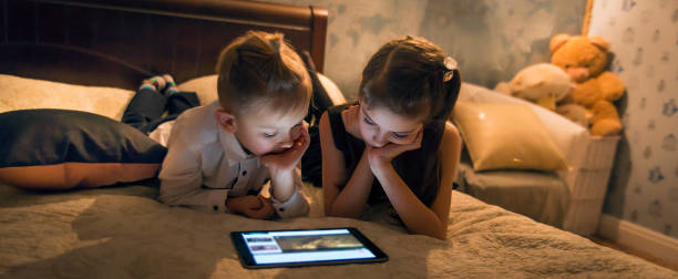 The kids are watching a movie on the tablet.Games and entertainment. stock photo