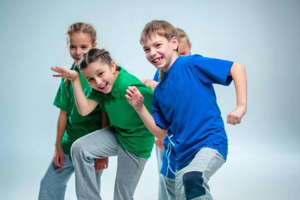 The kids dance school, ballet, hiphop, street, funky and modern dancers The kids dance school, ballet, hiphop, street, funky and modern dancers on gray studio background dance studio stock pictures, royalty-free photos & images