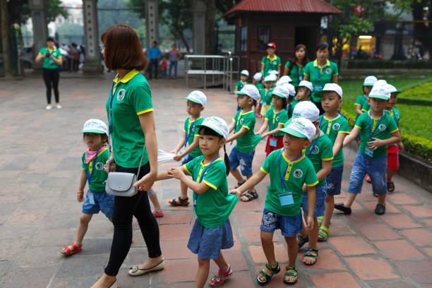 the kindergarten teachers lead children to visit the Temple of Literature (Van Mieu) stock photo