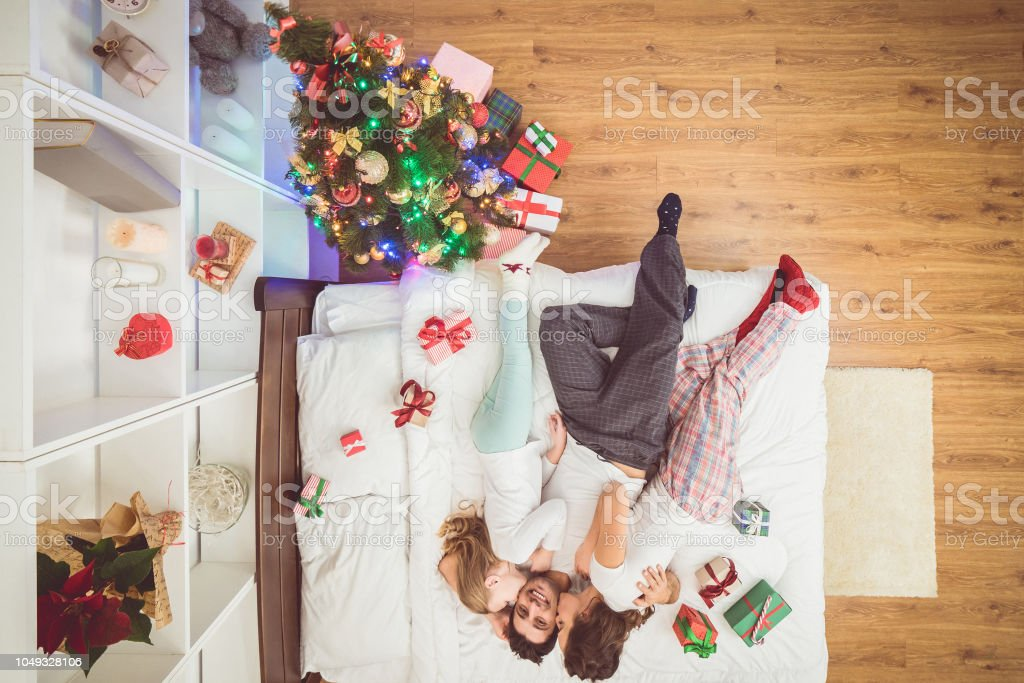 The Kissing Family Lay On The Bed With Gifts View From Above Stock