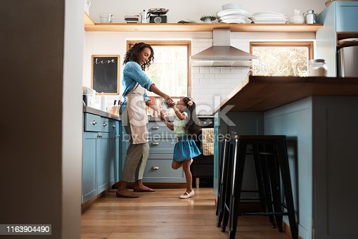 Shot of a young woman dancing with her daughter in the kitchen at home