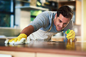 Cropped shot of a young man cleaning a kitchen surface at home