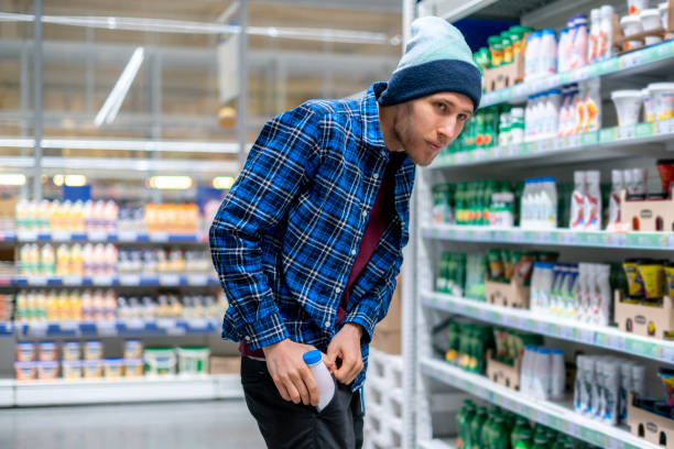 the kleptomania concept, a man in the grocery store stealing food and put it in the pocket stock photo