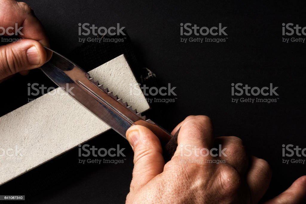 The knife during sharpening on the whetstone. stock photo