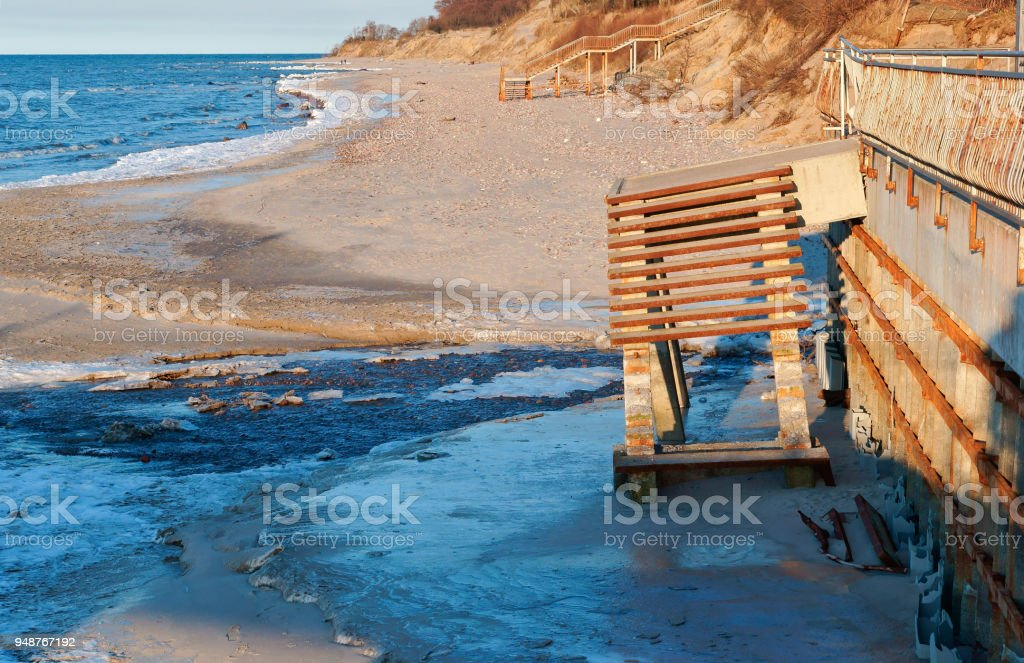 the ladder to the sea destroyed, the sea element spoiled ladder descent to the sea, the sea coast after a storm stock photo
