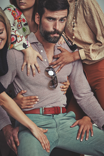 Studio shot of an attractive man in retro 70s wear surrounded and being touched by womenhttp://195.154.178.81/DATA/i_collage/pi/shoots/782690.jpg