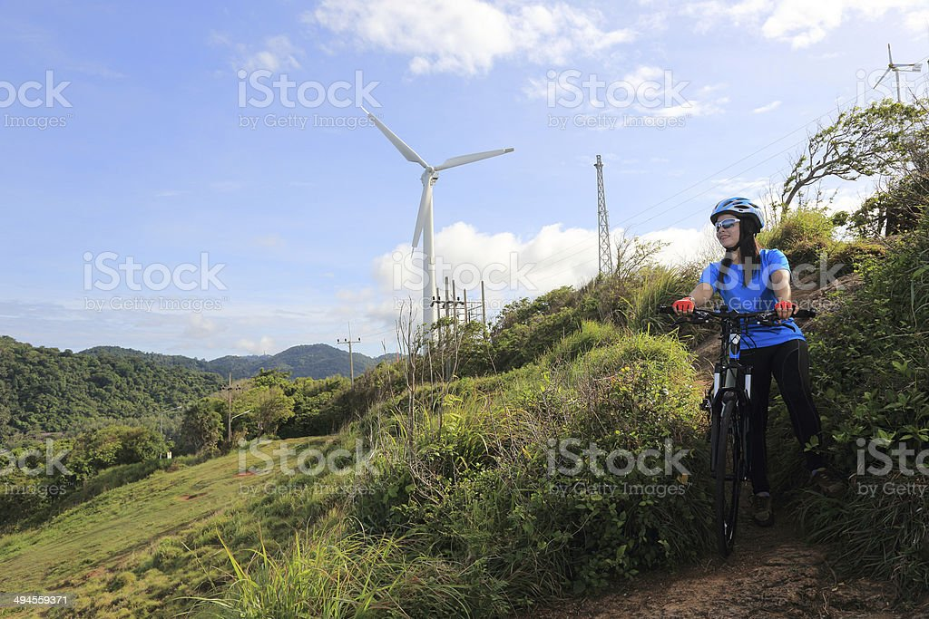 The lady is cycling downhill at windmill site stock photo