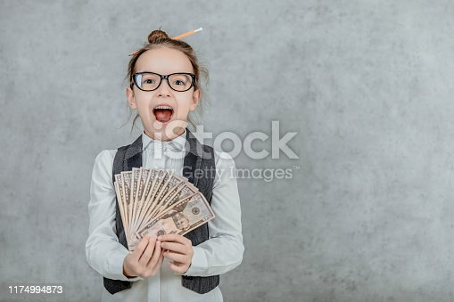 istock The lady's small business is on a gray background. Close-up During this, holds the money in hand. 1174994873