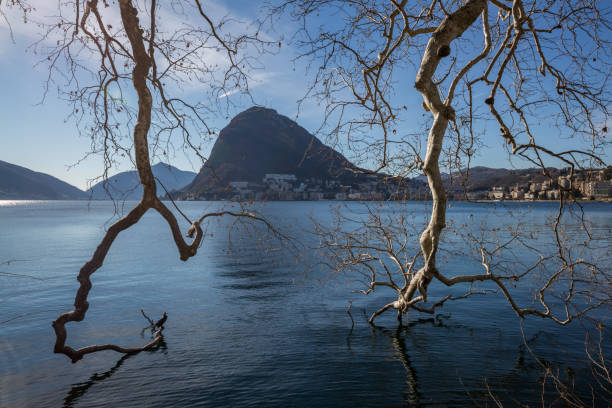 The lake of Lugano with misty sky and mountains at the distance stock photo