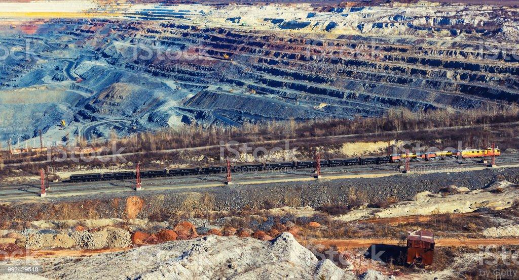 Le paysage d'une carrière de bauxite énorme avec les trains, les excavateurs de carrière et les camions à benne basculante - une vue d'ensemble par le haut - Photo