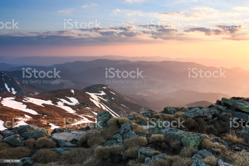 The landscape of the high mountains in snow. The grass and the rocks...