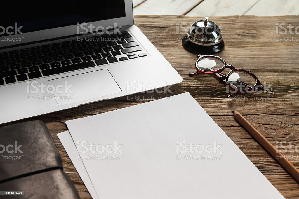 The laptop, blank paper, glasses and small bell on the stock photo
