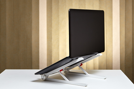 Adjustable portable aluminum laptop  holder folding with open pc notebook, back view.