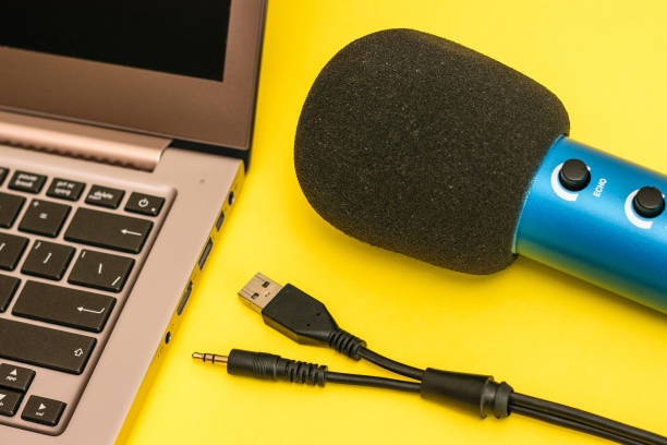 The laptop, the blue microphone and cord to connect the microphone on yellow background. stock photo