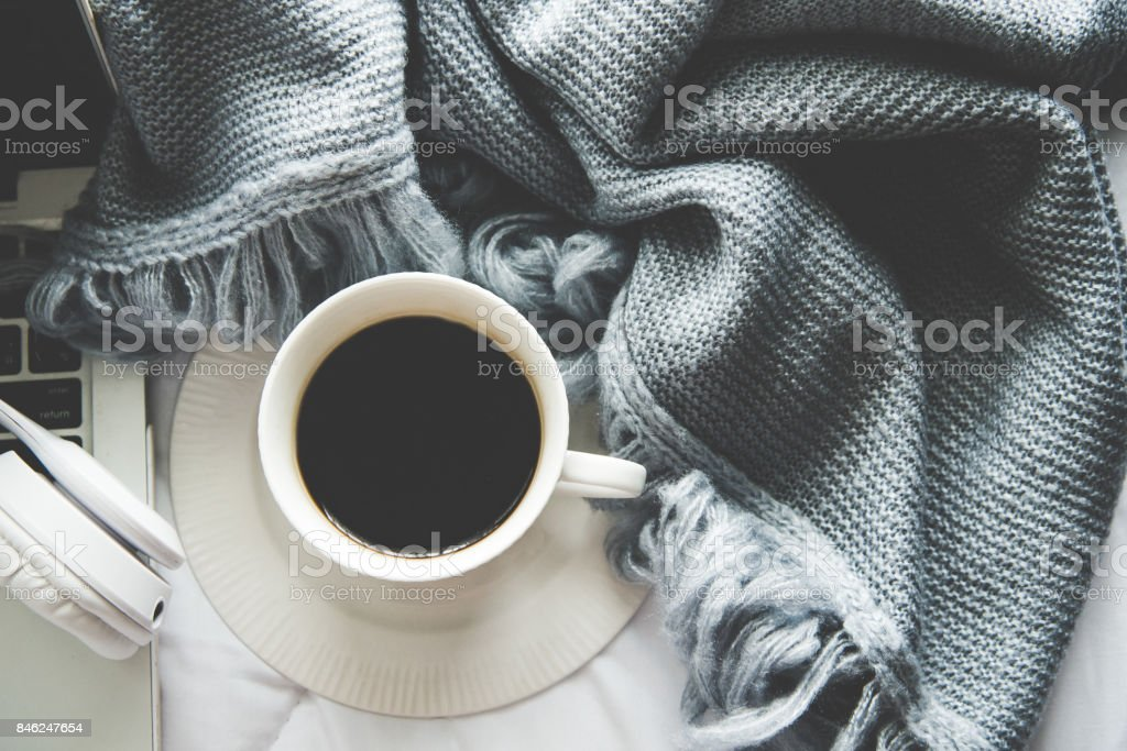 The laptop working and listen music on the white bed and coffee with marshmallow, warm knitted sweater in the sunny day.  Cozy winter home morning holiday.  Music and Lifestyle Concept. stock photo