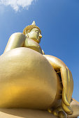 A close up picture of the large golden Buddha statue against a clouds and blue sky.