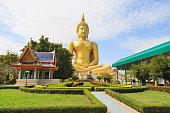 The large golden Buddha statue at Wat Muang against a clouds and blue sky.