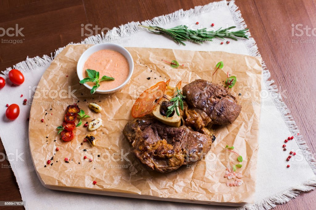 The large roasted piece of meat on the bone with sauce and spices on wooden board. View from top stock photo