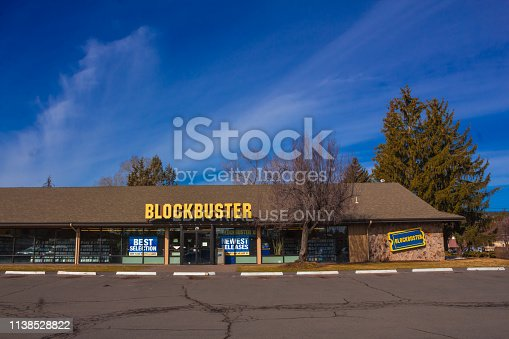 Oregon, USA 3/25/2019: The last Blockbuster store in the USA. The store is shown in the inside and also on the outside from the parking lot. Blockbuster LLC, formerly Blockbuster Entertainment, Inc.,and also known as Blockbuster Video or simply Blockbuster, was an American-based provider of home movie and video game rental services through a video rental shop, DVD-by-mail, streaming, video on demand, and cinema theater. Blockbuster expanded internationally throughout the 1990s. At its peak in 2004, Blockbuster employed 84,300 people worldwide, including about 58,500 in the United States and about 25,800 in other countries, and had 9,094 stores in total, with more than 4,500 of these in the US.
