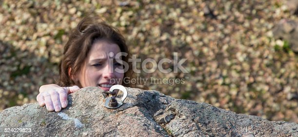 Brunette female climber tries to keep the hold. Very emotional face