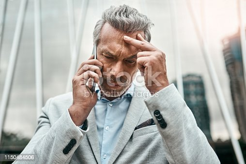 Shot of a mature businessman looking stressed out while talking on a cellphone in the city