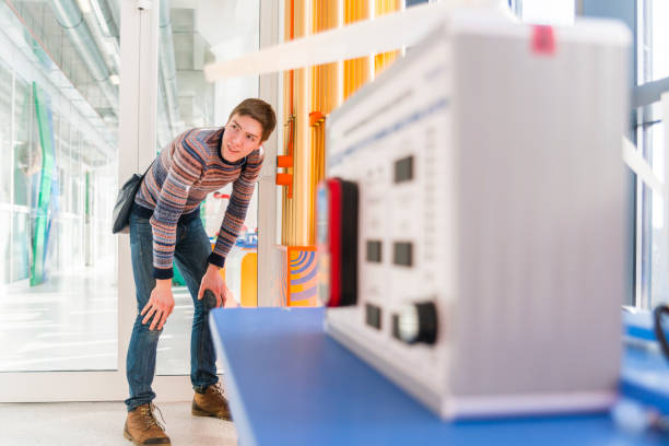 The late teenager boy exploring acoustic effects in the Hall of Science and Technology stock photo