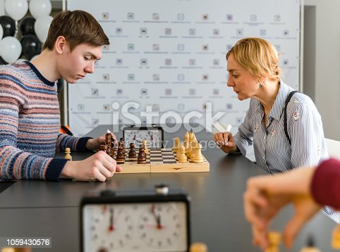 The late teenager boy playing chess with his mother on the tournament in the chess club