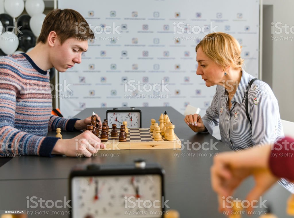 The late teenager boy playing chess with his mother on the tournament in the chess club stock photo