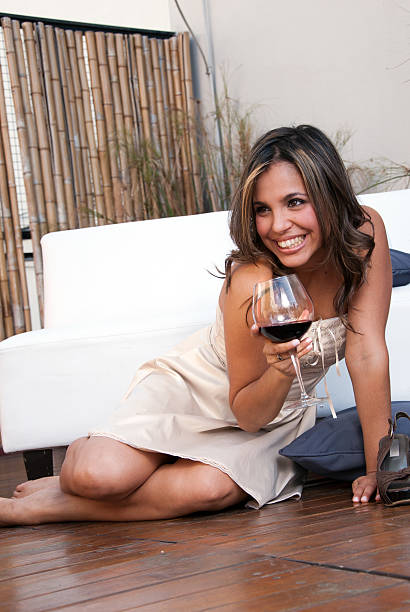 The laughing emotional Latin girl with wine stock photo