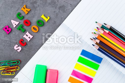istock The layout of school supplies on a dark gray background. The view from the top. Flat lay. Back to school. 1157053542