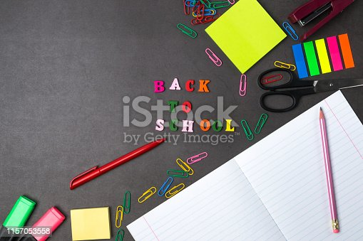 istock The layout of school supplies on a dark gray background. The view from the top. Flat lay. Back to school. 1157053558