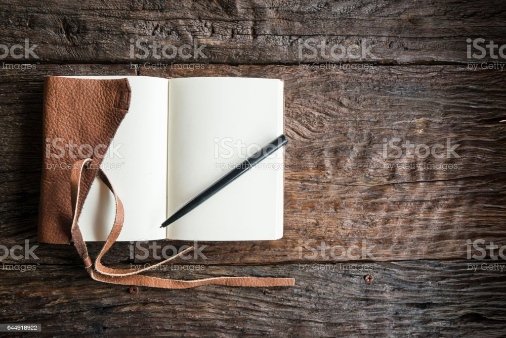 The leather book with pen on the wood table. stock photo
