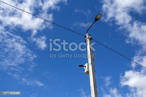 The LED street light is lined with a beautiful blue sky in the background with a video camera mounted on a pole. Video surveillance system.