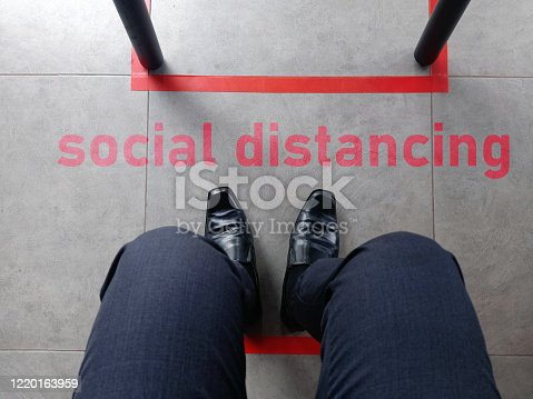 the leg of a man with black shoe and boutique trouser sitting in front of the word social distancing