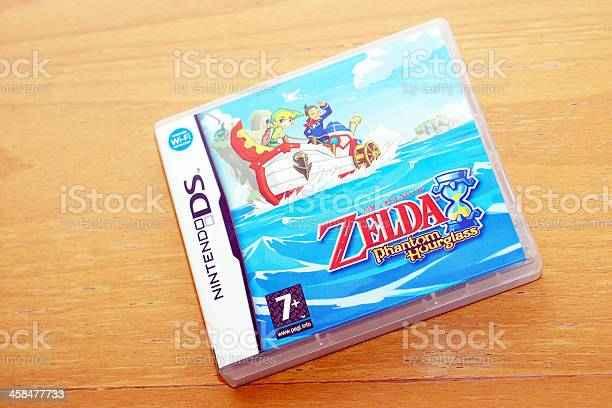 Liverpool, England - March 21, 2011: The Legend of Zelda: Phantom Hourglass game box for Nintendo DS videogame on wood table, studio shot. The Legend of Zelda​ is popular video game series created by Shigeru Miyamoto and Takashi Tezuka developed and published by Nintendo since 1986.