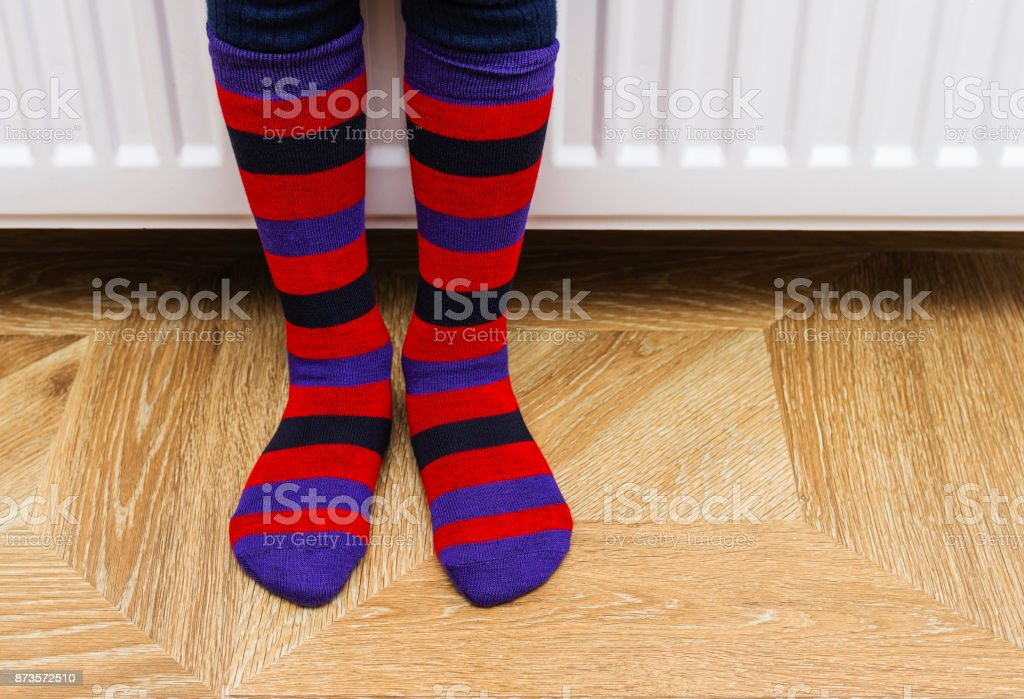 The legs of a child in bright striped socks against the background of a radiator stock photo