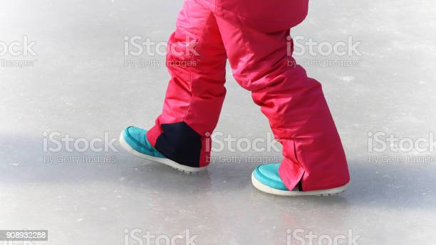 Photo of The legs of a girl walking on ice.