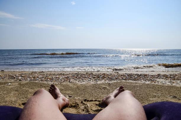 die beine eines mannes auf einem strand hintergrund. ein mann liegt auf einer amatrace am strand und ruht. beine in den rahmen. - türkise haare stock-fotos und bilder