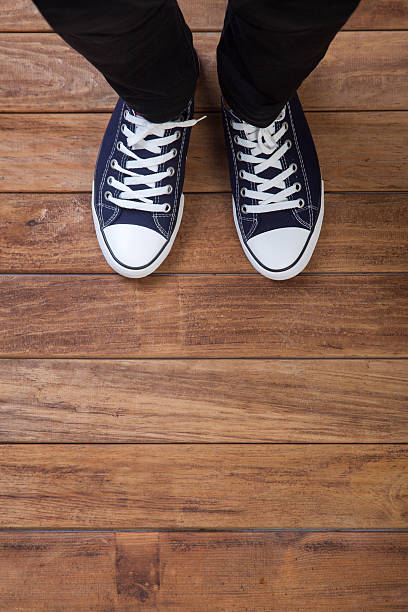 The legs of a man standing on wooden floor stock photo