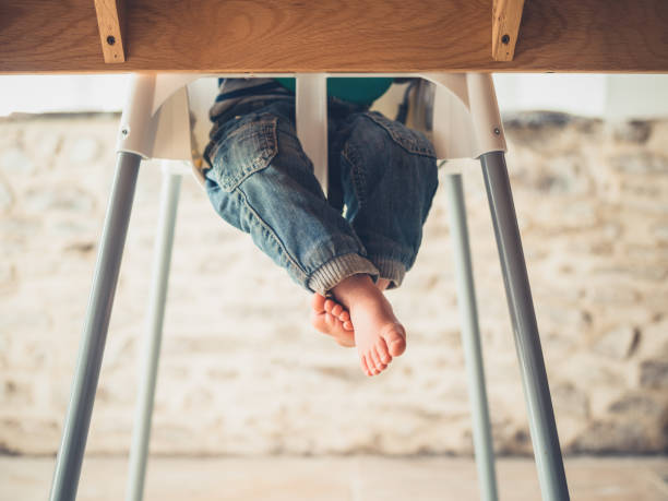 The legs of a toddler in a high chair at the table stock photo