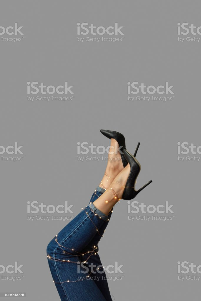 The legs of a woman in high-heeled shoesare, stretched out decorated with a Christmas garland on a gray background. stock photo