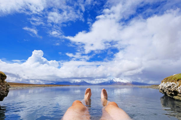 The legs of an athletic man in natural thermal hot spring Polloquere, Salar De Surire salt lake, Isluga Volcano National Park, Chile stock photo