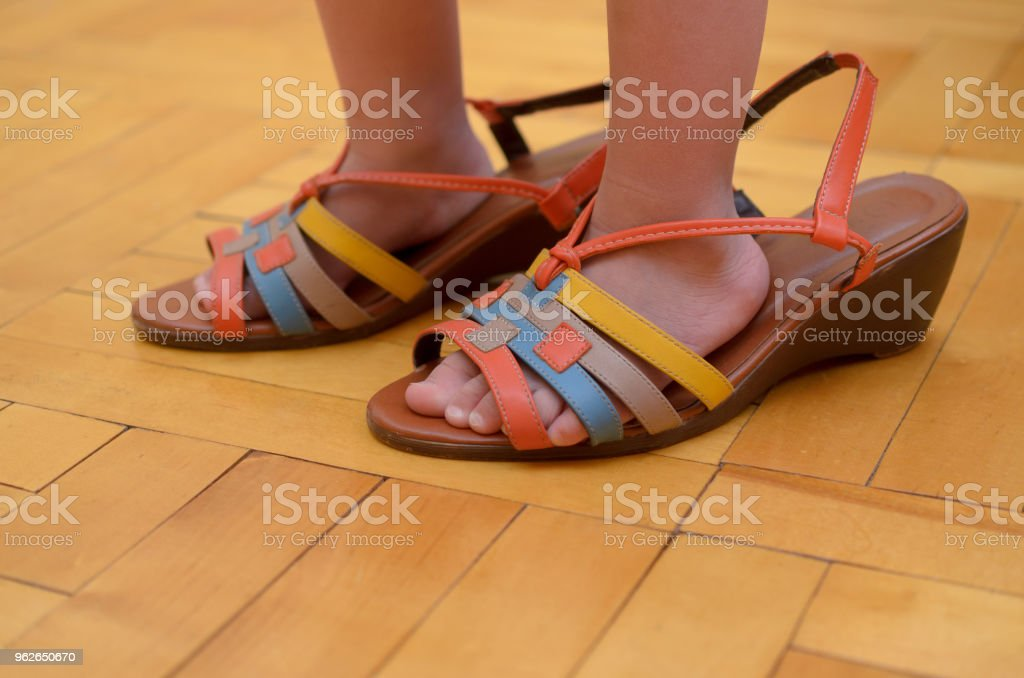 The legs of the little girl are shod in the big mom's shoes. - foto stock