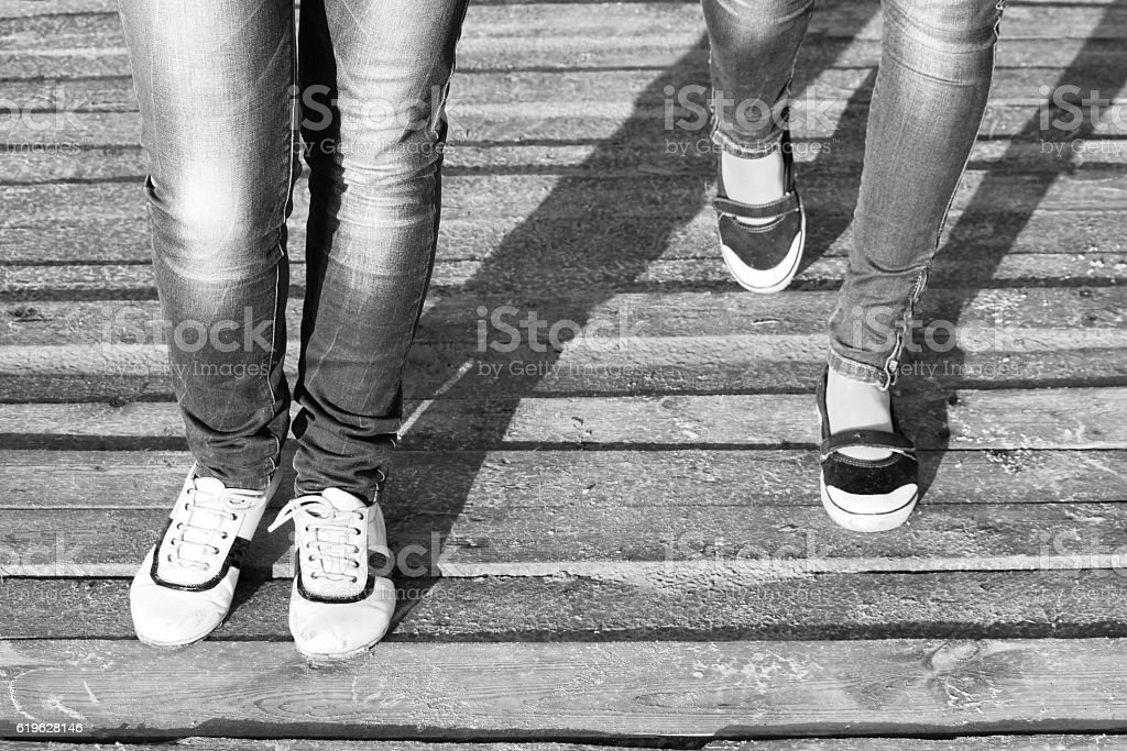 The legs of two girls in jeans and comfortable shoes stock photo