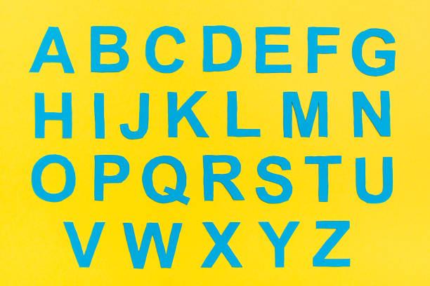 İngiliz alfabesinin harfleri mavi kartondan kesilir. stok fotoğrafı