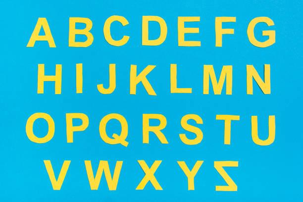 İngiliz alfabesinin harfleri sarı kartondan kesilir. stok fotoğrafı
