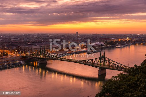 The historical Liberty Bridge of Budapest from Gellert Hill before sunrise, with dramatic vibrant sky.